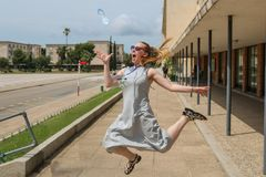 Blonde girl jumping, catching a water bottle stock photography