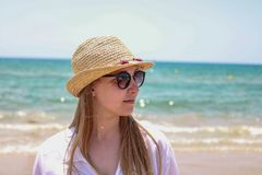Blonde woman with hat and sunglasses on the sea royalty free stock photography