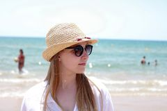 Blonde woman with hat and sunglasses on the sea stock images