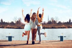 Shoot of three beautiful girls outdoors by the river. Female friends relaxing by the river and smiling. Girlfriends stock photo