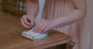Bride putting wedding rings in decorated box. Shoot of two wedding rings in a box on table stock footage