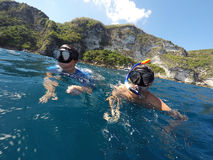 Shoot of a young boy snorkeling with father. Young boy snorkeling with father in a tropical sea in Nusa penida, Indonesia, Bali Royalty Free Stock Photos