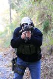 Shooter. A man shooting/aiming an assault/tactical rifle at a target to the right of the photographer. There is also a pistol on his right hip Royalty Free Stock Image