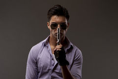 Shooter with gun and gloves. Medium shot of shooter or contractor wearing glasses and holding gun near face Stock Image