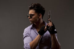 Shooter with gun looking right on grey background. Stylish shooter or contractor with gun, glasses gloves and big hair Royalty Free Stock Photo