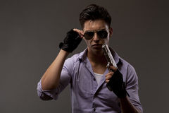 Shooter with gun removing glasses Royalty Free Stock Photo