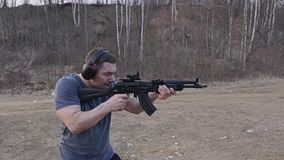 The shooter makes a series of shots from a black assault rifle on the shooting range. Side view. The camera is in motion. Slow mo with sound stock video