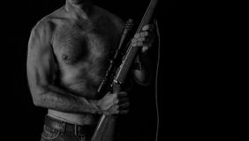 Shooter with Rifle. Sniper rifle with scope and shirtless man. possibly a terrorist. Low key black and white image Stock Photo