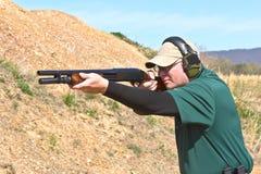 Shooter with Shotgun. A man at a shooting range firing a shotgun for sport Royalty Free Stock Image
