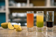 Shooters drinks. Three short cocktail on a bar background, concept for drinks offers at promotional evenings. Cocktails with lime. Shooters drinks. Three Stock Images