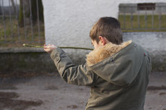 Shooting. Young boy shooting with a stick, pretending it is a gun Stock Photos