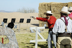 Shooting Action 1. Competitor shooting a single-action pistol in a cowboy shoot competition Stock Image