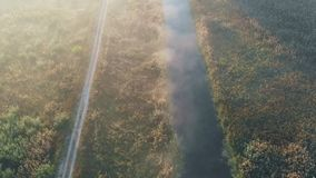 Shooting from the air, flying over the river with which the road passes nearby stock video footage