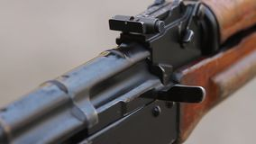 Shooting from the AK. Closeup of the gate and safety lock assault rifle, two shots in slow motion stock video