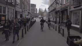 Shooting the Amsterdam`s typical street with old buildings and bicycle traffic and pedestrians stock video