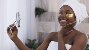 Shooting of attractive young African woman with towel on head and medical golden patches under eyes, smiling while stock footage