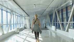 Shooting from back woman walks down hallway. Blonde woman walking in terminal waiting room indoors. Shooting from back passenger walks down hallway at airport stock video footage