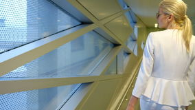 Shooting from back passenger walks down hallway at airport stock footage