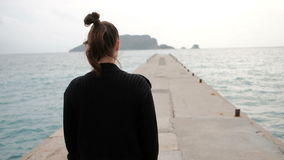 Shooting from back woman walking on sea shore looking into distance stock video footage