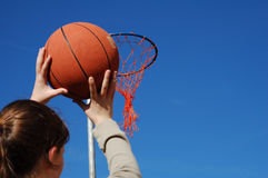 Shooting A Basket. Young teenage girl taking aim with a basketball ready to score Royalty Free Stock Image