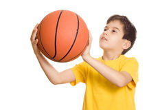 Shooting a basketball. A young basketball player sets up for the shot- focus on the basketball royalty free stock images