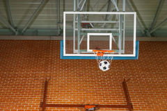 Shooting a basketball goal with a soccer ball. Passing through the net on an indoor court in a conceptual image stock photos