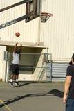 Shooting basketball at hoop royalty free stock image