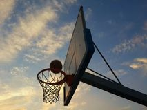 Shooting basketball. Shoot basket net sport fitness active exercise trainings workout sky clouds ball hoop board glass player moving bucket play playing nba star Royalty Free Stock Photography