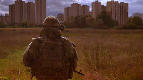 Shooting from behind, walking soldier in camouflage, is leading to skyscrapers, holding gun, crossing path, dark. Background, melancholic authentic illustration stock footage