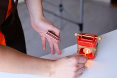 Shooting close-up of hand of male masseur who creates aromatic a. Male therapist doctor holds matches in his hands and lights aromatic candle in special stand Stock Photography