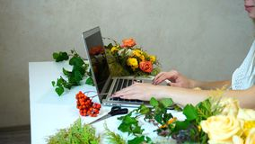 Close-up of hands of flower designer girl working on laptop on t stock image