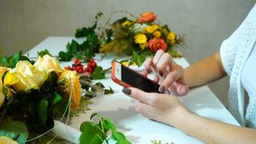 Close-up of smartphone and hands of female florist who drives royalty free stock photography