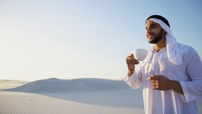 Portrait of handsome young Arabian Sheikh who drinks from cup of. Shooting close-up portrait of attractive and happy Muslim man who enjoys aroma of coffee and Royalty Free Stock Images
