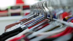 Shooting clothes woman hangers constantly in store indoors. Close up Shot clothing in score, long line with black rack stock video