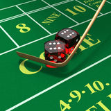 Shooting craps or dice on green felt background. Craps dice roll called any craps, hi-lo, boxcars, midnight with stickman's mop or whip on green felt table with Stock Photos