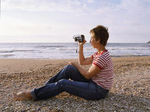 Shooting de la mujer por la videocámara foto de archivo libre de regalías
