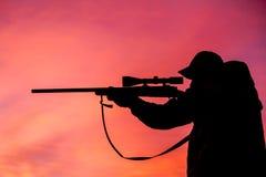 Shooting del cazador del rifle en la salida del sol Fotografía de archivo