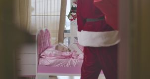 Shooting through doorway of cute Caucasian girl sleeping in pink bed as Santa Claus coming into the room with red gift