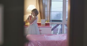 Shooting through doorway of little Caucasian girl coming up to pink bedside table and taking casket. Cute child looking stock footage