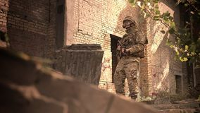 Shooting from the down corner, caucasian soldier is standing still and glancing at camera, holding gun, camouflage and. Helmet wearing, brick wall on background stock video
