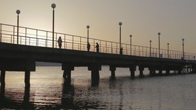 Shooting with drone at sunset in a bay. The drone passes under a pier. N stock footage