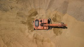 Aerial photo of excavator on sand. On the construction site top view. stock photography