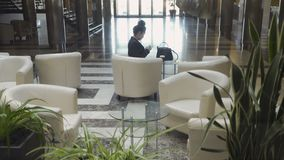 Shooting from elevator: stylish businesswoman sits in a lobby hall in hotel. Shooting from elevator: it moves down. Stylish businesswoman sits in a lobby hall in stock video footage