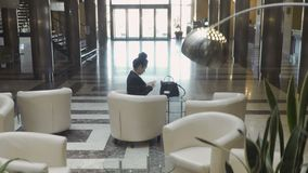 Shooting from elevator: elegance businesswoman use phone sitting in a lobby hall. Shooting from elevator: it moves up. Stylish businesswoman sits in a lobby hall stock video