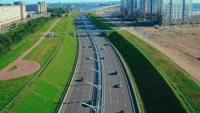 Shooting from flying drone car driving on highway past residential building. Aerial shooting from flying drone car driving on highway past residential buildings stock footage