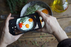 Shooting food on phone`s camera, Fried eggs in an old pan with tomatoes on a wooden table, Selective focus, Food Photographer, Clo stock photo