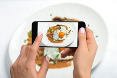 Shooting food on phone`s camera, Fried eggs on a white plate with mushroom on a white table, Food Photographer. Royalty Free Stock Images