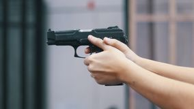 Shooting gallery. A young man holding a gun and shooting. Close up hands stock video