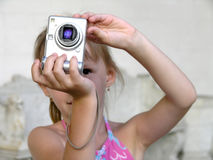 Shooting girl. Close-up little girl shooting with digital camera Stock Photography
