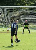Shooting for Goal. Striker and goalkeeper in a football game stock photography